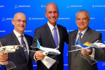 3 men holding airplane models